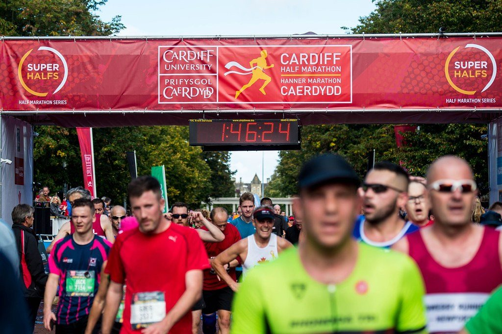 The finish line of Cardiff half marathon with multiple runners finishing