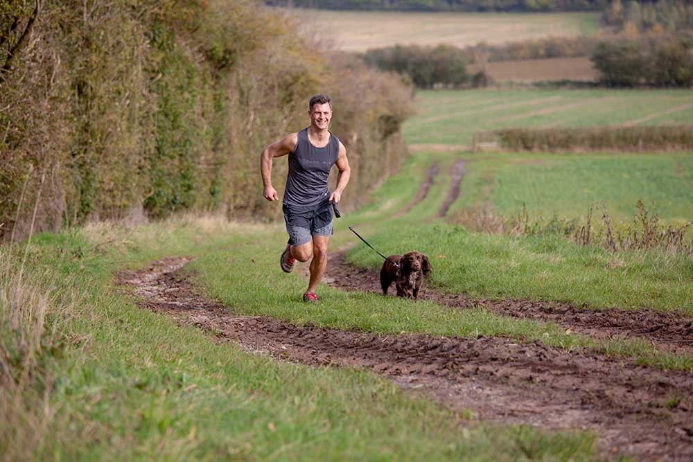 Male runner in a field with a dog on a lead running beside him