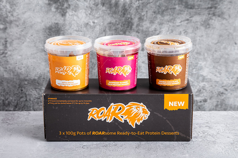 Trio of ROAR high protein desserts, a source of whey protein on the go. Pictured on a black ROAR box against a grey marble background