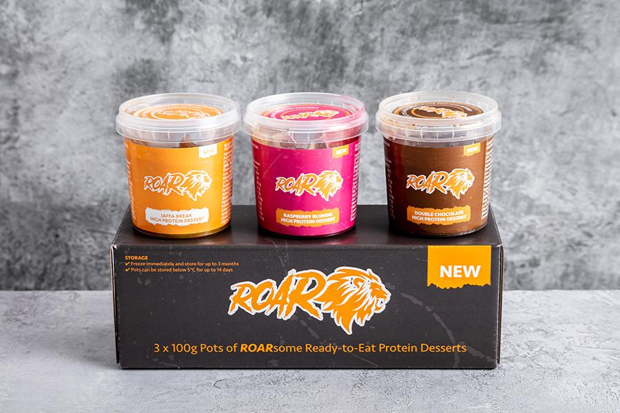 Trio of ROAR high protein desserts on a black ROAR box against a grey marble background