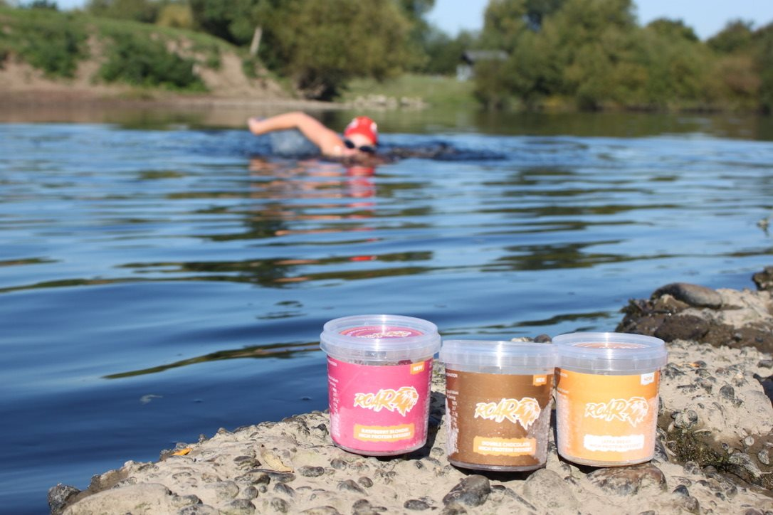 Swimmer in a river with three ROAR protein pots in the foreground