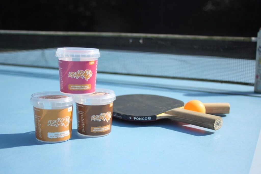 ROAR protein review image of three pots of protein dessert of different flavours set alongside a pingpong bat on a table tennis table