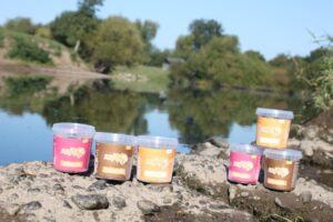 Six pots of ROAR protein of all three flavours placed on rocks beside a river with trees reflecting in the water and blue sky