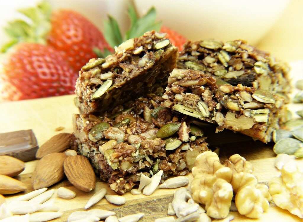 Three seeded granola bars stacked up with nuts in the foreground and strawberries behind