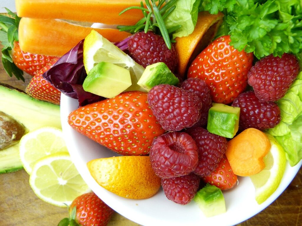 Fruit salad is a good option for a low saturated fat dessert. Strawberries, raspberries and citrus fruit combine with salad leaves displayed overflowing from a white bowl.