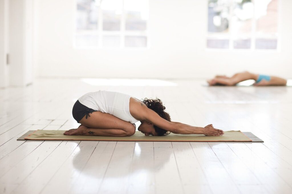 Lady with dark hair wearing a white t-shirt and black shorts in a forward bending pose on the floor in a yoga class