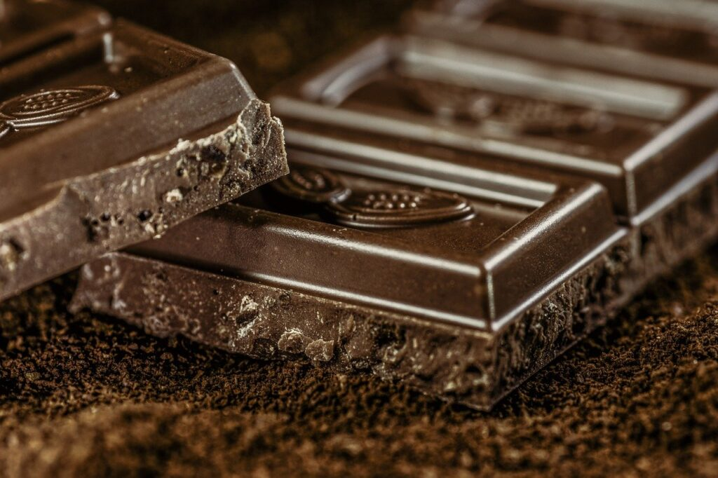 Pieces from a bar of dark chocolate on a dark brown background