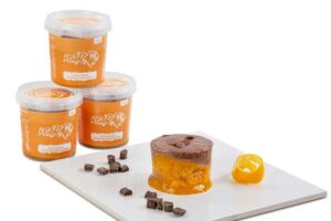 Jaffa cake desserts - three ROAR high protein Jaffa break desserts piled up with one emptied out in foreground on white tile